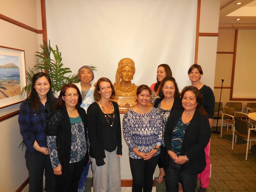 キャンサーナビゲーター資格を取得したGHC会長のアキよしかわ(後段向かって左)と研修の同窓生一同。中央の胸像はクィーンズメディカルセンターを創設したエマ女王